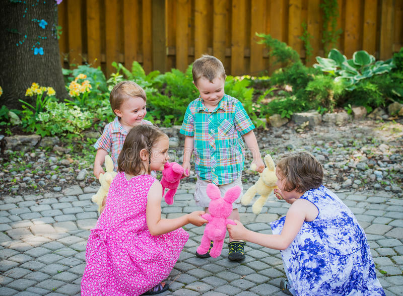 Children Playing Ring Around the Rosie Game. Girls and boys are holding hands together in a circle playing a fun game of ring around the rosie holding colorful royalty free stock images