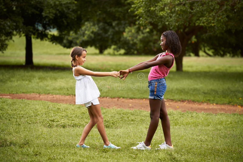 Children playing ring around the rosie in park. Two hispanic and african little girls playing ring around the rosie in public park and holding hands royalty free stock photography