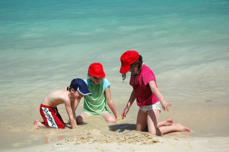 Children playing in the sand. Three children on tropical beach, nikon D70 royalty free stock image