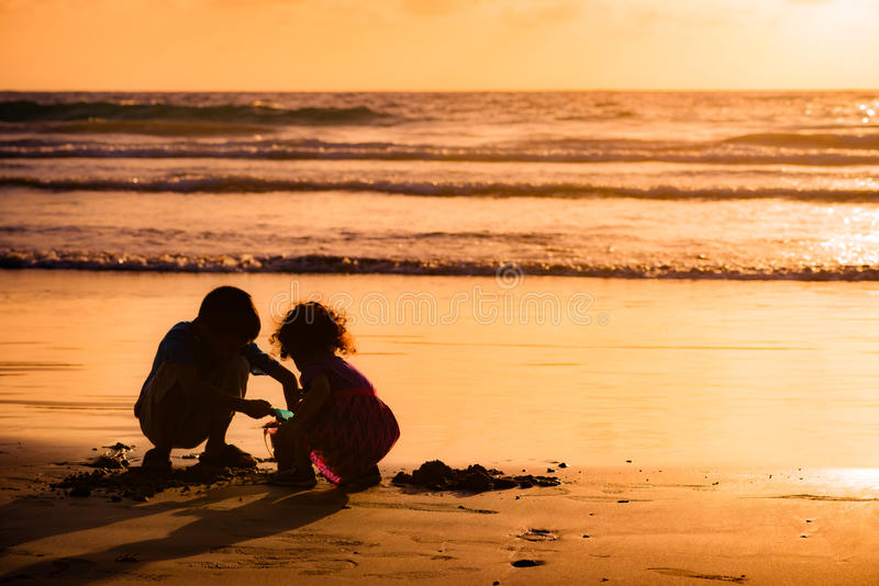 Children playing with sand by the sea at sunset in Tobago royalty free stock image