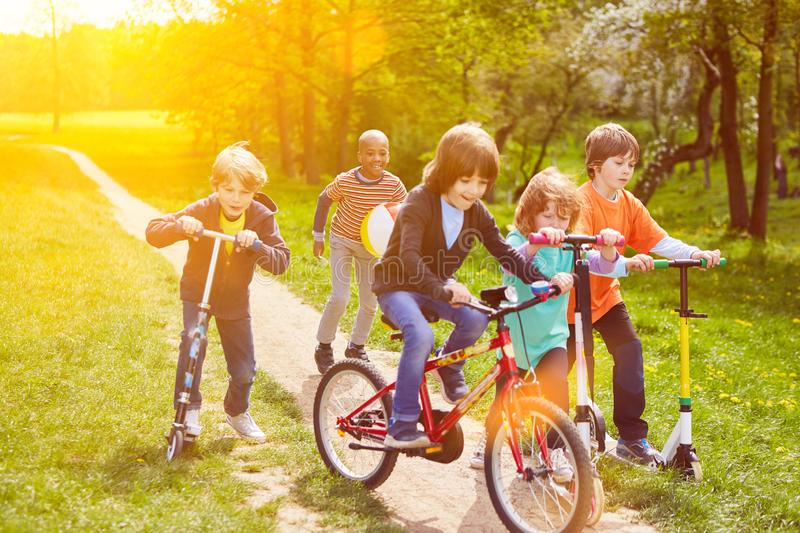 Children playing with scooters and bicycles. Playing children ride together with scooter and bike in the park stock images
