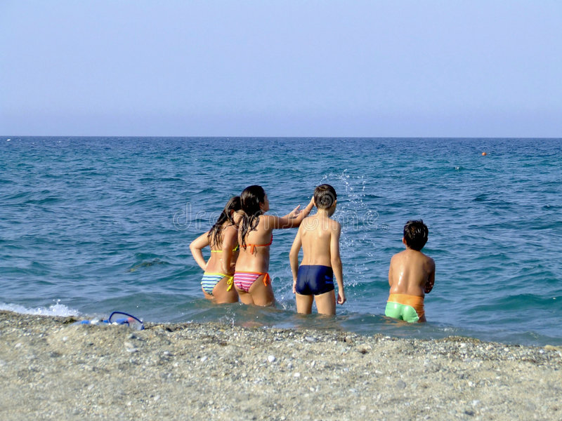 Children playing in the sea stock photography