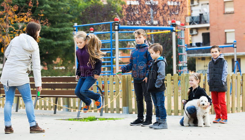 Children playing skipping rope. Girl jumping with skipping rope among friends at city street royalty free stock photo