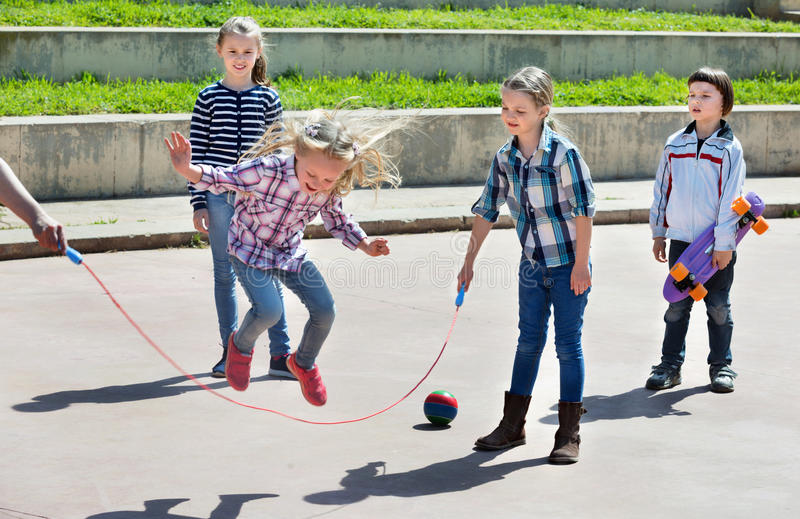 Children playing skipping rope jumping game. Happy positive children playing skipping rope jumping game and laughing outdoors royalty free stock images