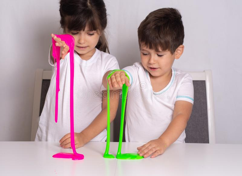 Child playing with slime. Kids squeeze and stretching slime. stock image
