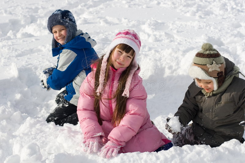 Children Playing In Snow. Young girl and her two brothers playing in snow stock image