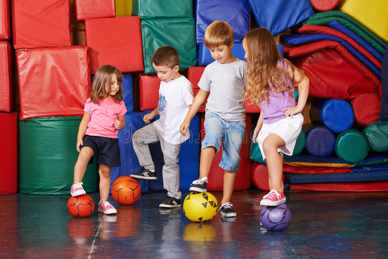 Children playing soccer in gym stock image