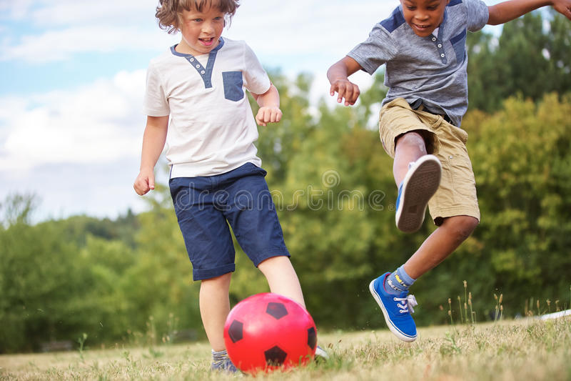 Children playing soccer stock images