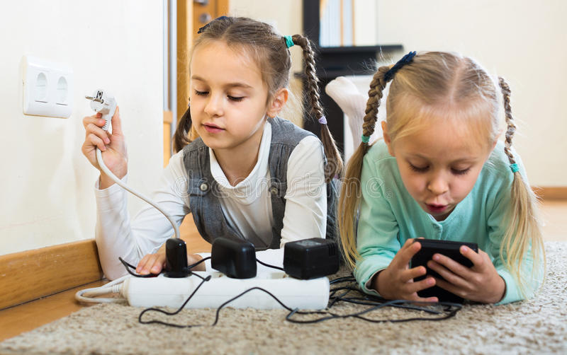 Children playing with sockets and electricity indoors. Careless little children playing with sockets and electricity indoors royalty free stock images