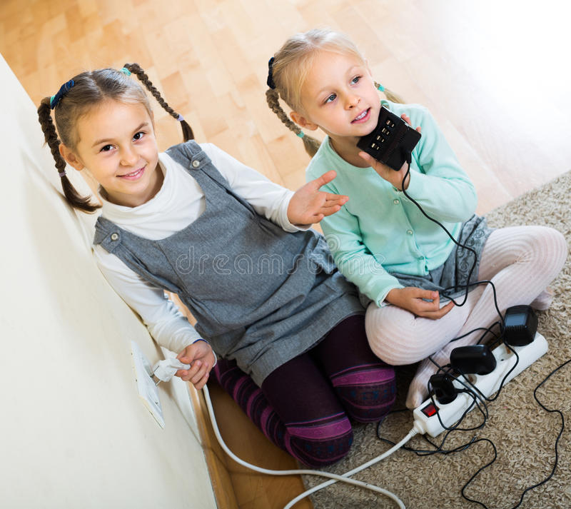 Children playing with sockets and electricity indoors. Positive children playing with sockets and electricity indoors royalty free stock photos