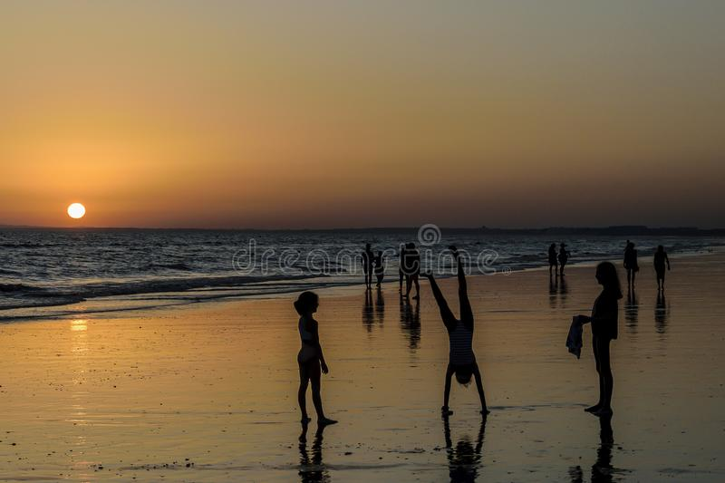Children playing at sunset on the beach stock images
