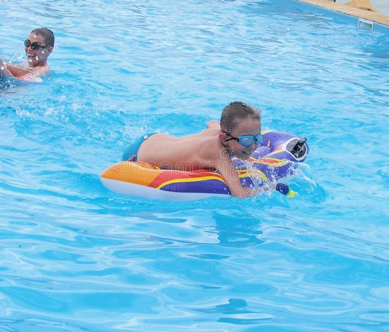 Children playing in the swimming pool stock photography