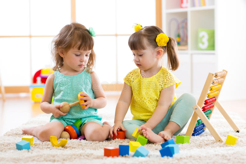 Children playing together with building blocks. Educational toys for preschool and kindergarten kids. Little girls build. Pyramid toys at home or daycare royalty free stock image