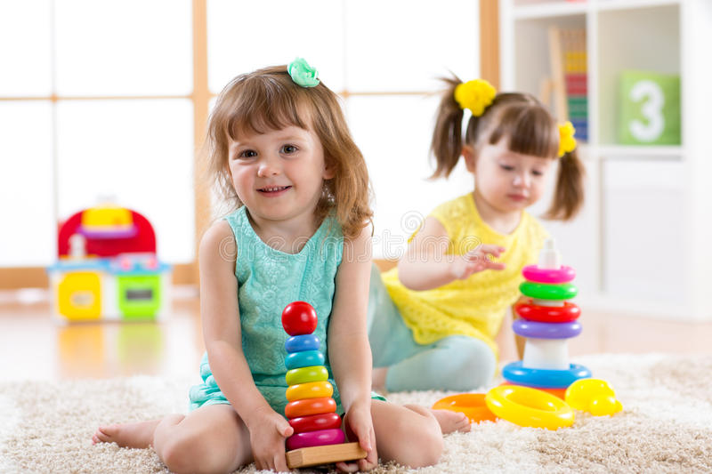 Children playing together. Educational toys for preschool and kindergarten kids. Little girls build pyramid toys at home royalty free stock photo
