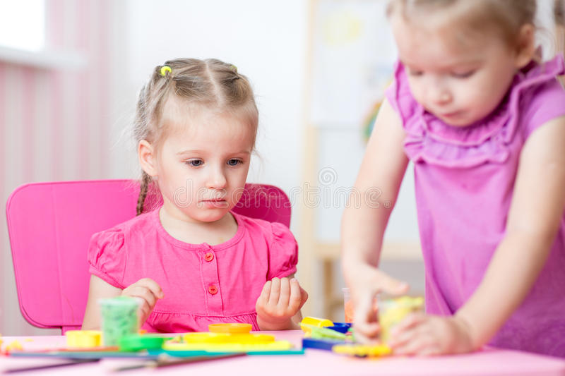 Children playing together in nursery royalty free stock image