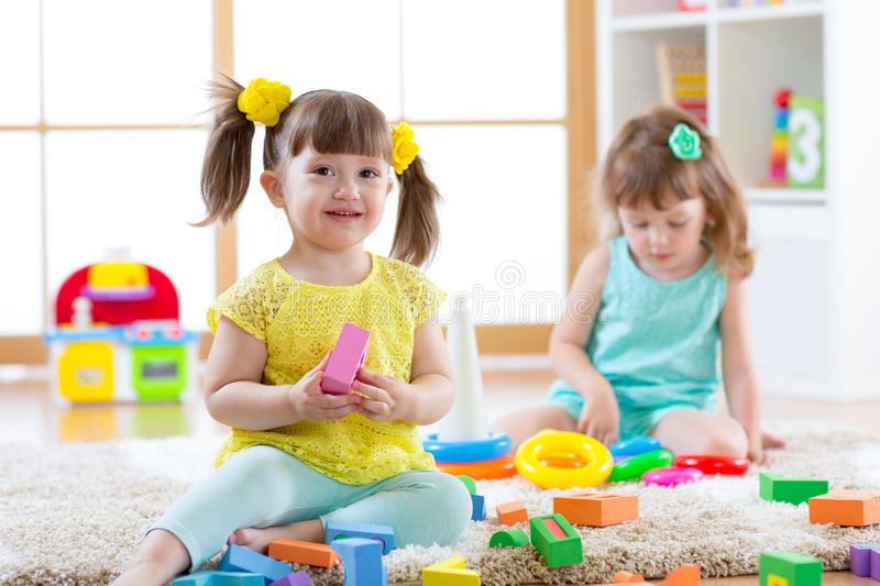 Children playing together. Toddler kids play with blocks. Educational toys for preschool and kindergarten child. Little royalty free stock photo