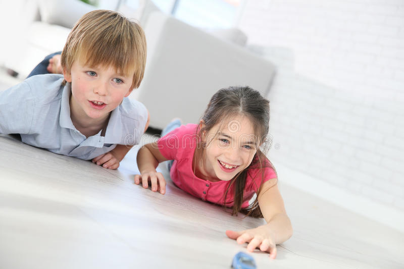 Children playing with toy cars at home. Kids playing with toy cars laying on floor royalty free stock photos