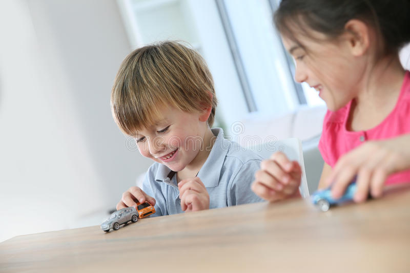Children playing with toy cars. Kids playing with toy cars at home stock photo
