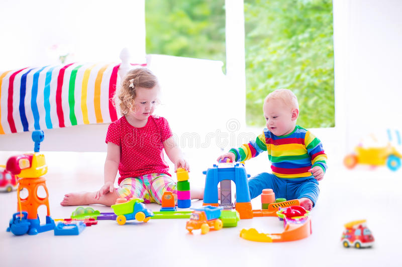 Children playing with toy cars. Two happy children playing with toy cars, cute curly toddler girl and a funny baby boy, brosther and sister, sitting on the floor stock photo