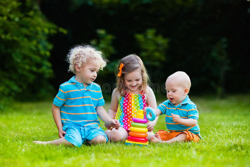 Children playing with toy pyramid. Three little children play with colorful rainbow pyramid toy. Educational toys for young child. Sibling kids building tower stock photos
