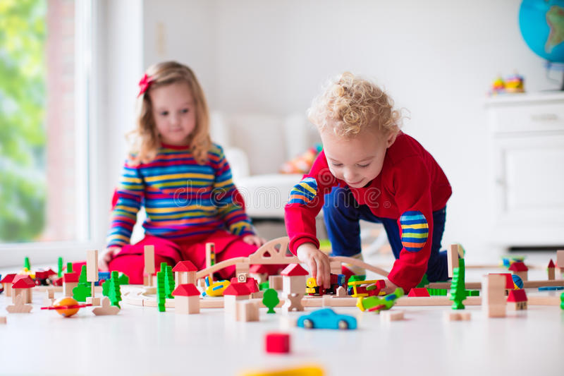 Children playing with toy railroad and train. Children playing with wooden train. Toddler kid and baby play with blocks, trains and cars. Educational toys for stock image