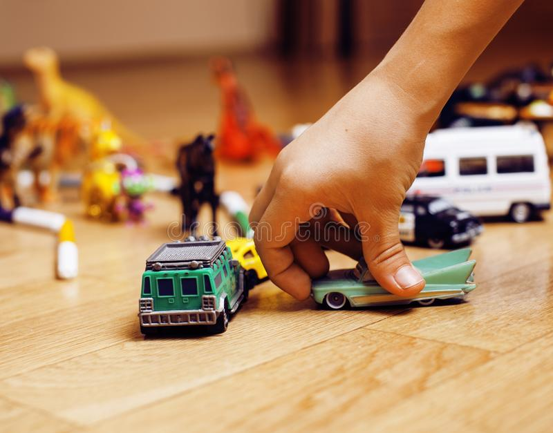 Children playing toys on floor at home, little hand in mess, free education. Closeup stock image