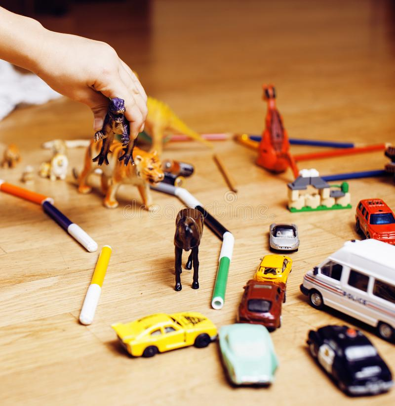 Children playing toys on floor at home, little hand in mess, free education, lifestyle people concept. Closeup stock photo
