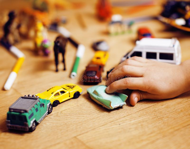 Children playing toys on floor at home, little hand in mess, free education, lifestyle people concept. Closeup royalty free stock photo