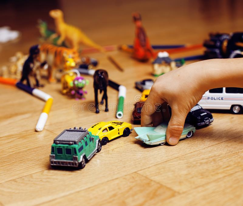 Children playing toys on floor at home, little hand in mess, free education, lifestyle people concept. Closeup stock image