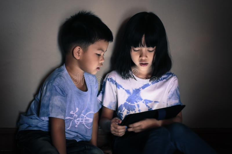 Children playing and using tablet together. stock image