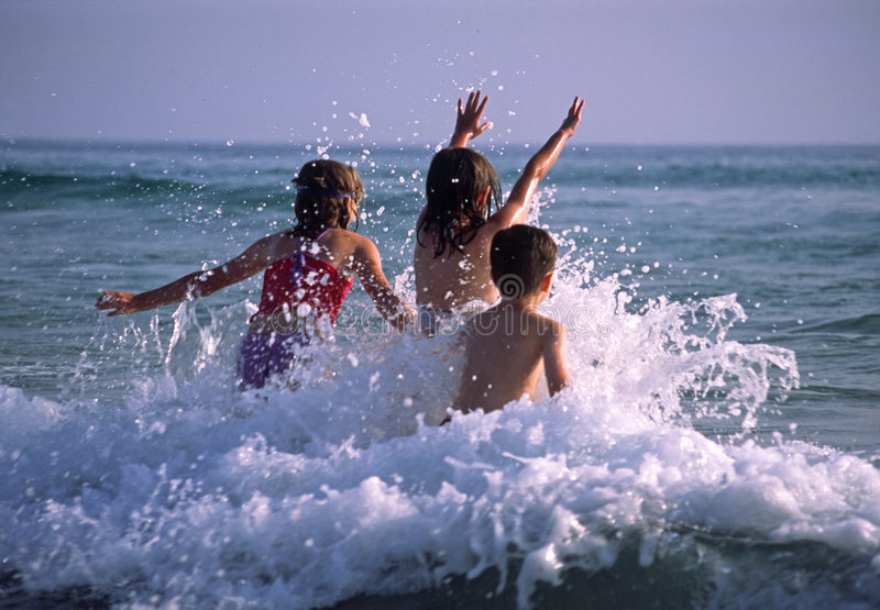 Children playing in the waves stock photography