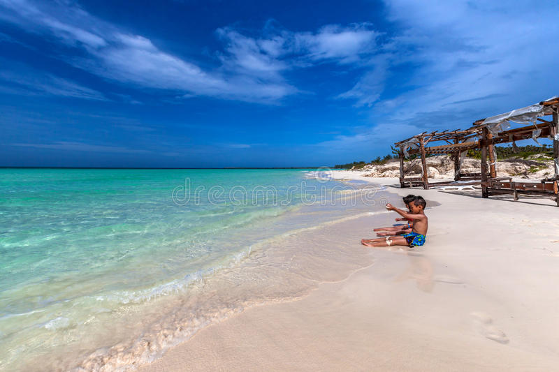 Children playing on white sandy Cuban beach in Cayo Coco. Pristine white sandy Cuban beach in Cayo Coco stock photo