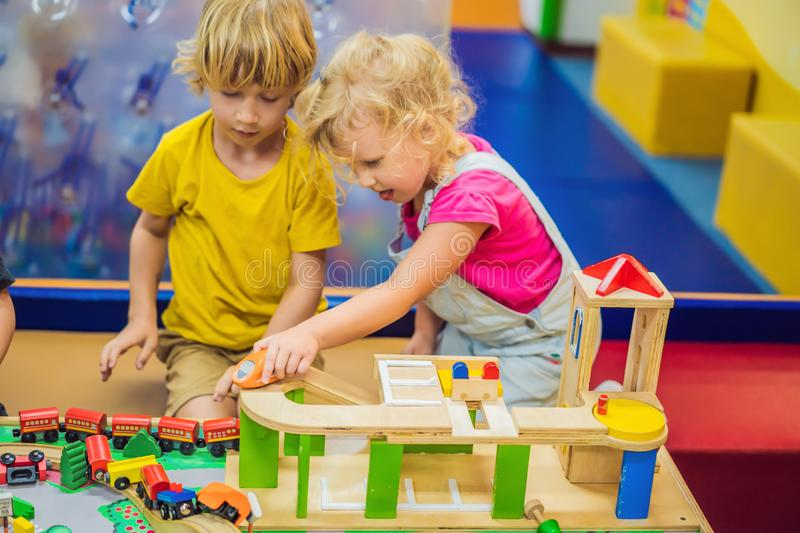 Children playing with wooden train. Toddler kid and baby play with blocks, trains and cars. Educational toys for. Preschool and kindergarten child. Boy and girl royalty free stock images