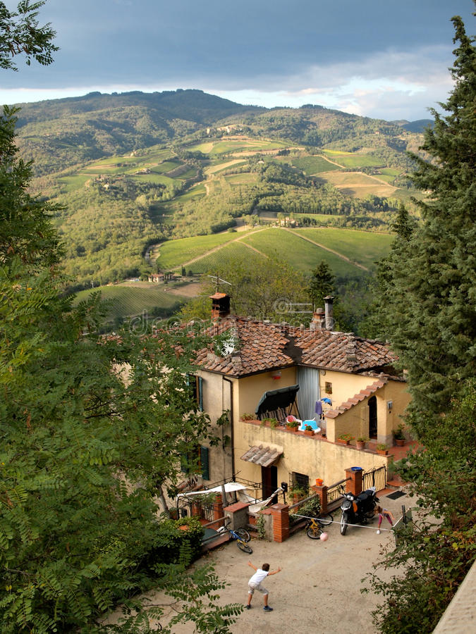 Children playing in a yard among Tuscan landscape stock image