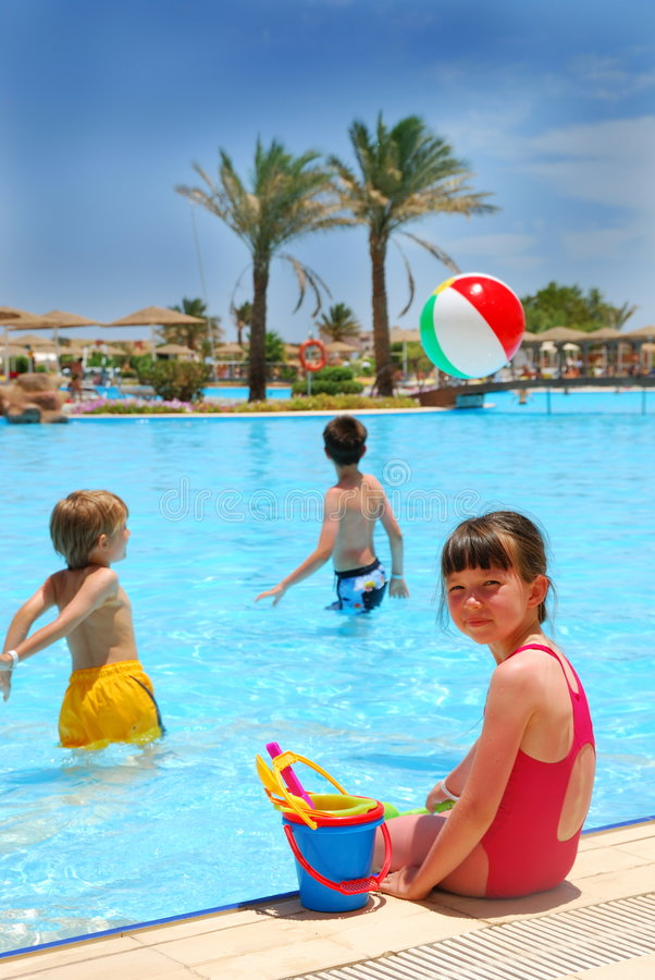 Children In Pool. Three children playing in a pool - a little girl is sitting on the side with toys, while two boys are in the water. Beach ball is hovering over royalty free stock photos