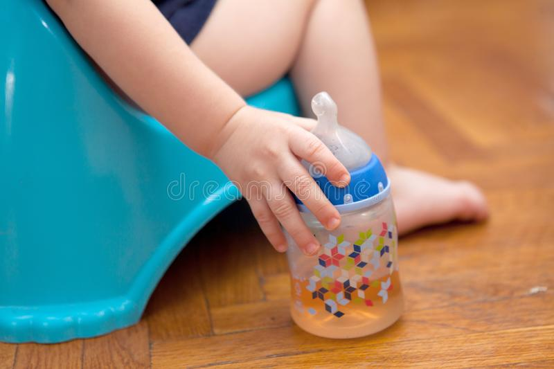 Children in a pot hold a pacifier on the background of parquet royalty free stock images