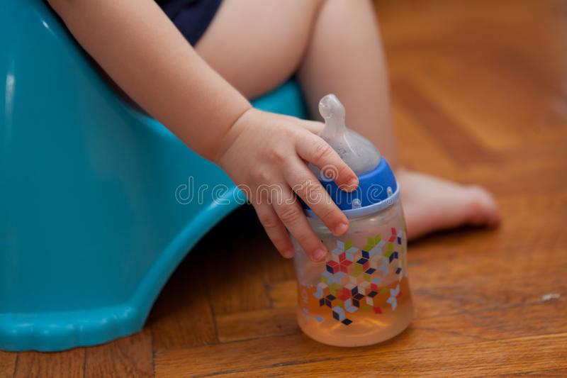Children in a pot hold a pacifier on a brown background stock images