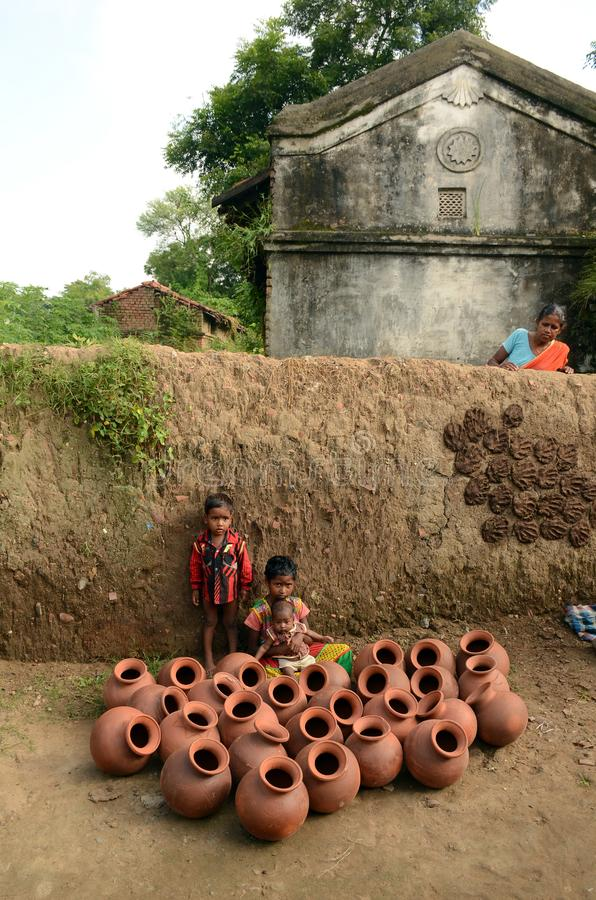 Children Of The Potter. Potter children are playing infront of many clay pots at the remote village in India royalty free stock images
