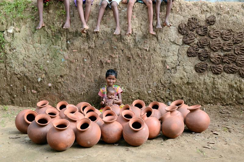 Children Of The Potter. Potter children are playing infront of many clay pots at the remote village in India royalty free stock photo
