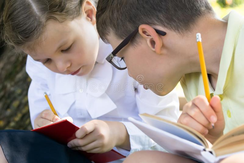 Children prepare for exams sitting outside in good weather after class royalty free stock photo