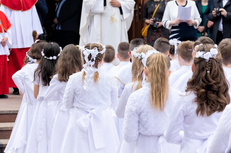 Children prepared for the first communion are waiting in front of the church royalty free stock image