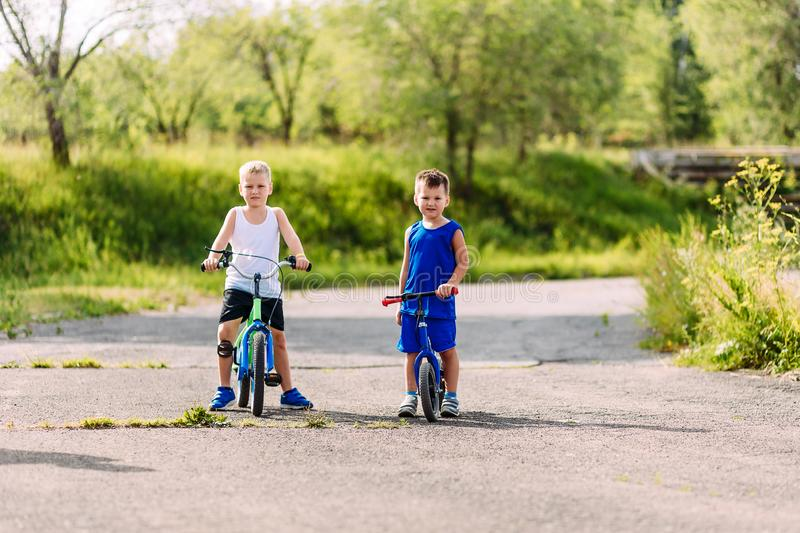 Children preschoolers ride bicycles in the summer in the Park. On the pavement stock photo