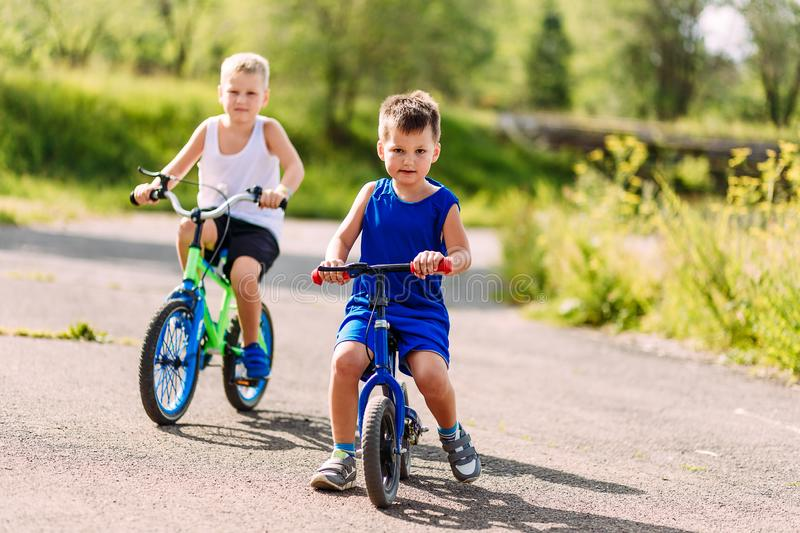 Children preschoolers ride bikes in the summer in the Park on the pavement. Boy on the jogger royalty free stock photos