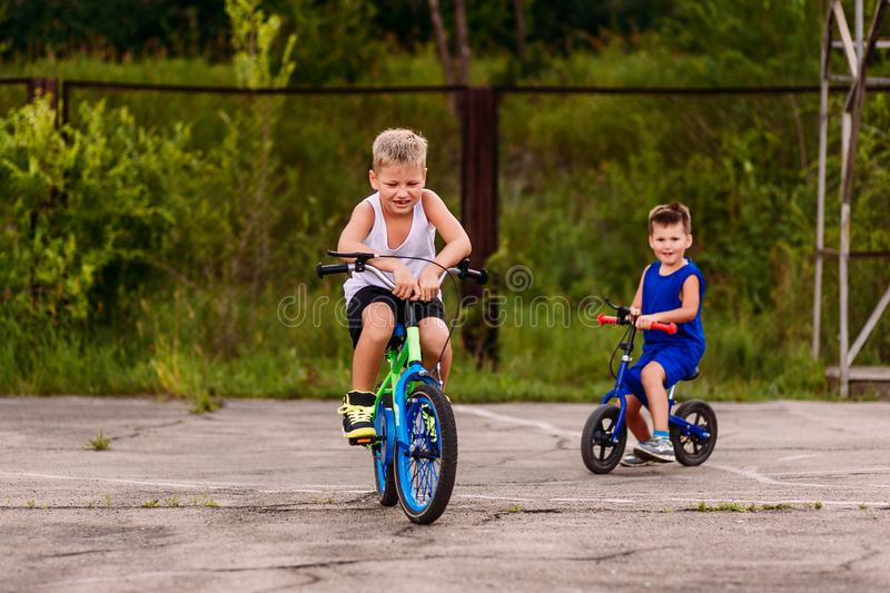 Children preschoolers ride a two-wheeled bike on the paved area in the summer. Children and sports. Happy children preschoolers ride a two-wheeled bike on the royalty free stock image