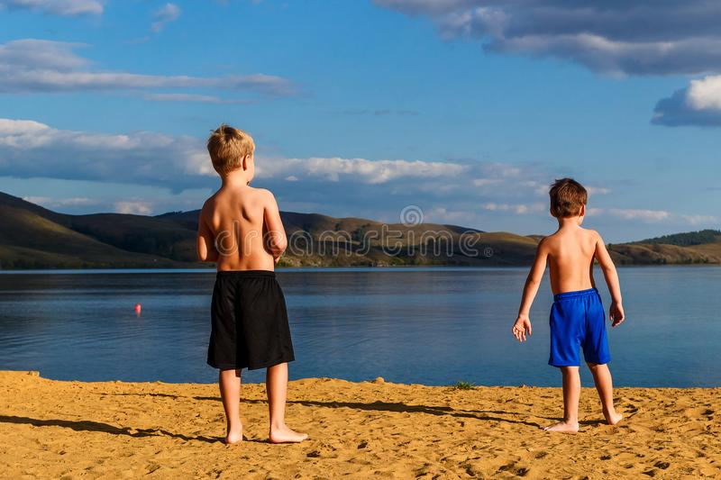 Children preschoolers stand barefoot on the yellow sand on the beach back to the camera. In the summer stock images
