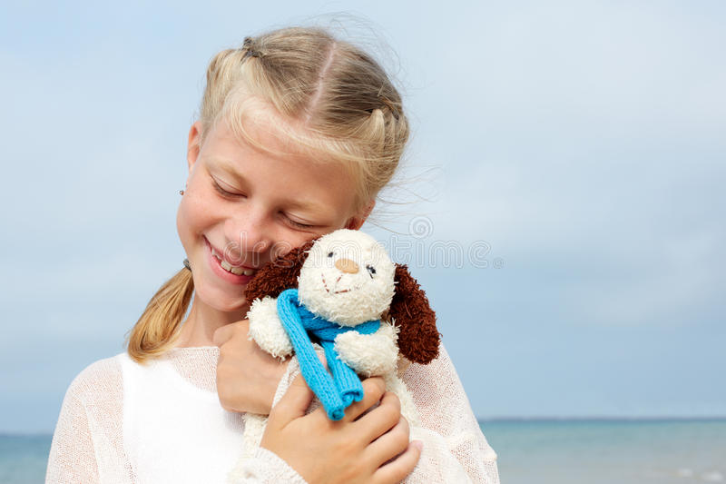 Children psychology. The little beautiful girl embraces an amusing dog - toy. Favorite soft toy. stock photography