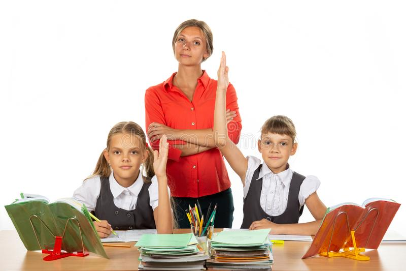 Children pull their hands up, ready to answer a question, in the background a satisfied teacher stock images