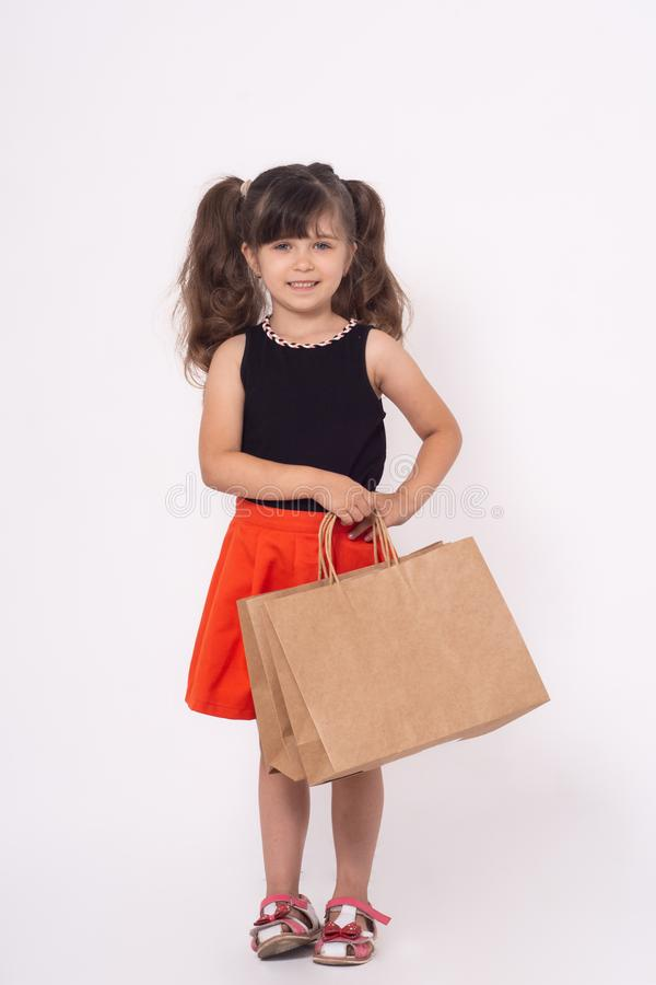 Children with purchases isolated on white background. Kid with shopping bags. stock images