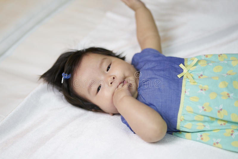The children put a finger in his mouth to sleep on the couch, white. stock images