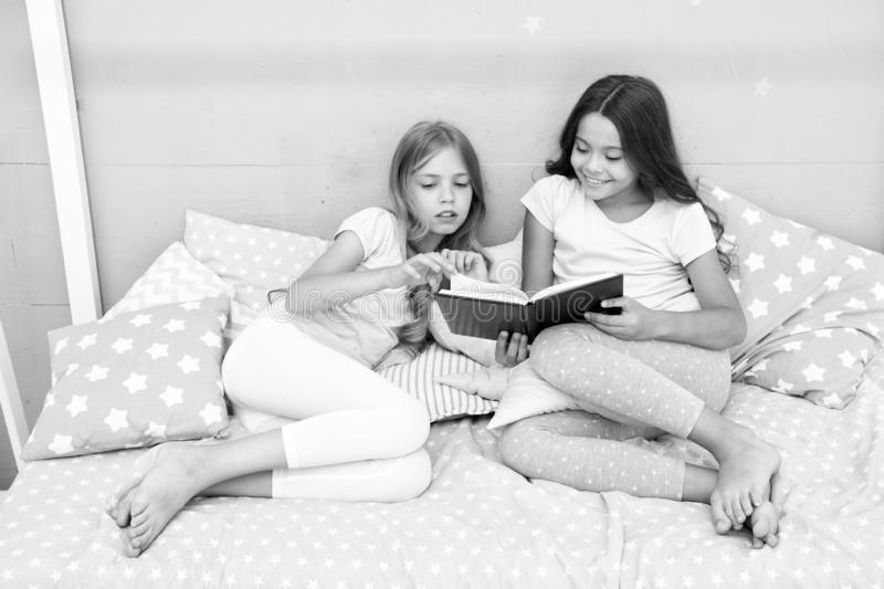Children read book in bed. Family tradition. Girls best friends read fairy tale before sleep. Best books for kids. Reading before bed can help sleep better at stock image